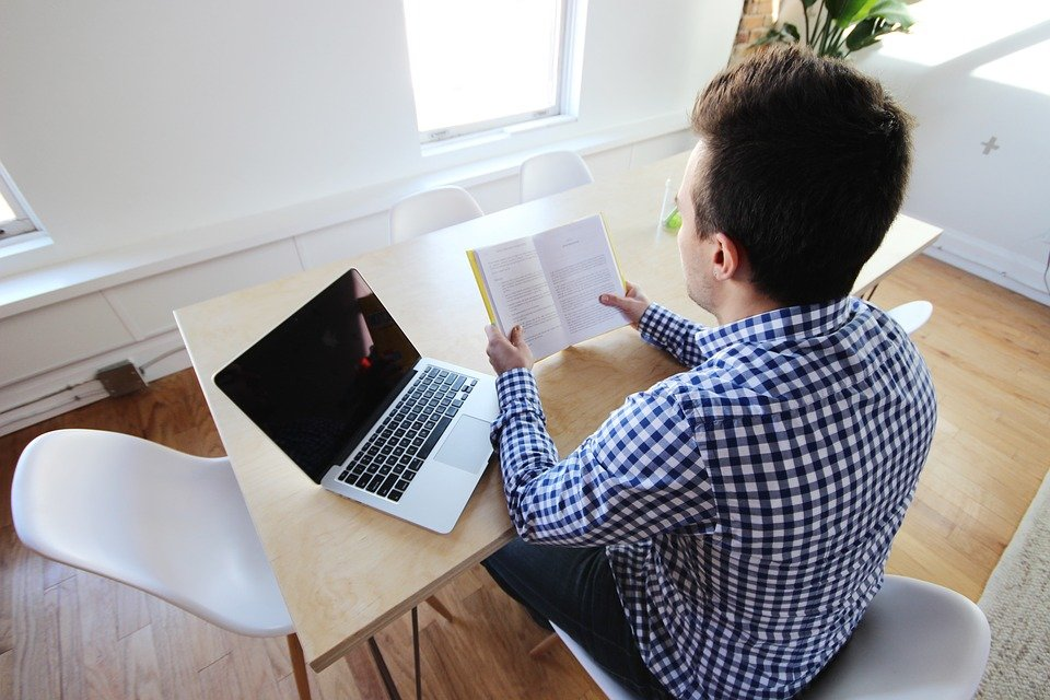 man reading a book with a laptop on his side