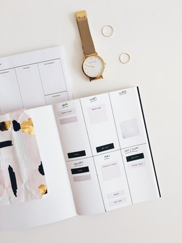 round gold-colored watch beside white planner