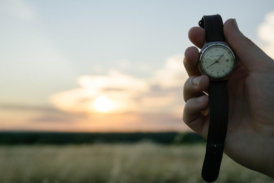 holding a watch while watching the sunrise
