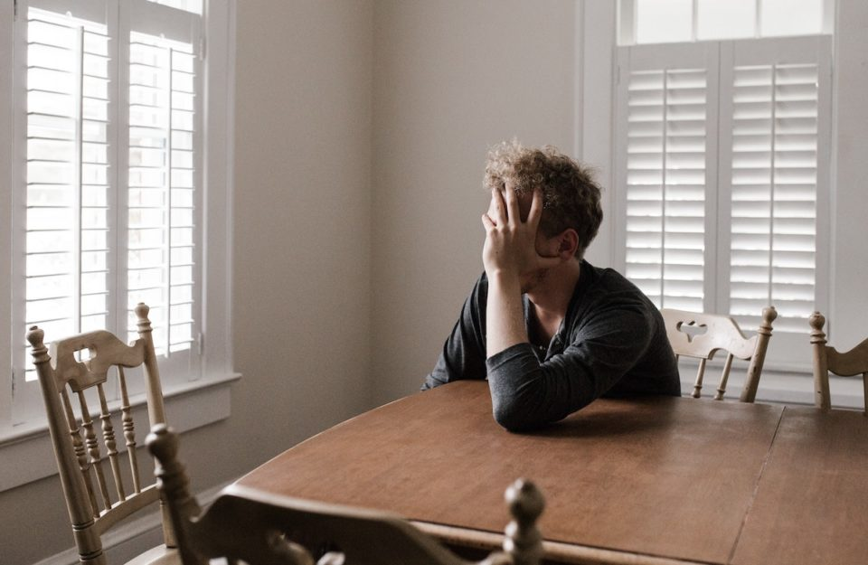 Man crying over money staring out the kitchen window.