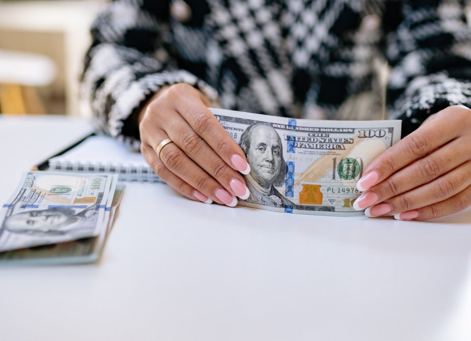Woman holding stack of money with hundred dollar bills.