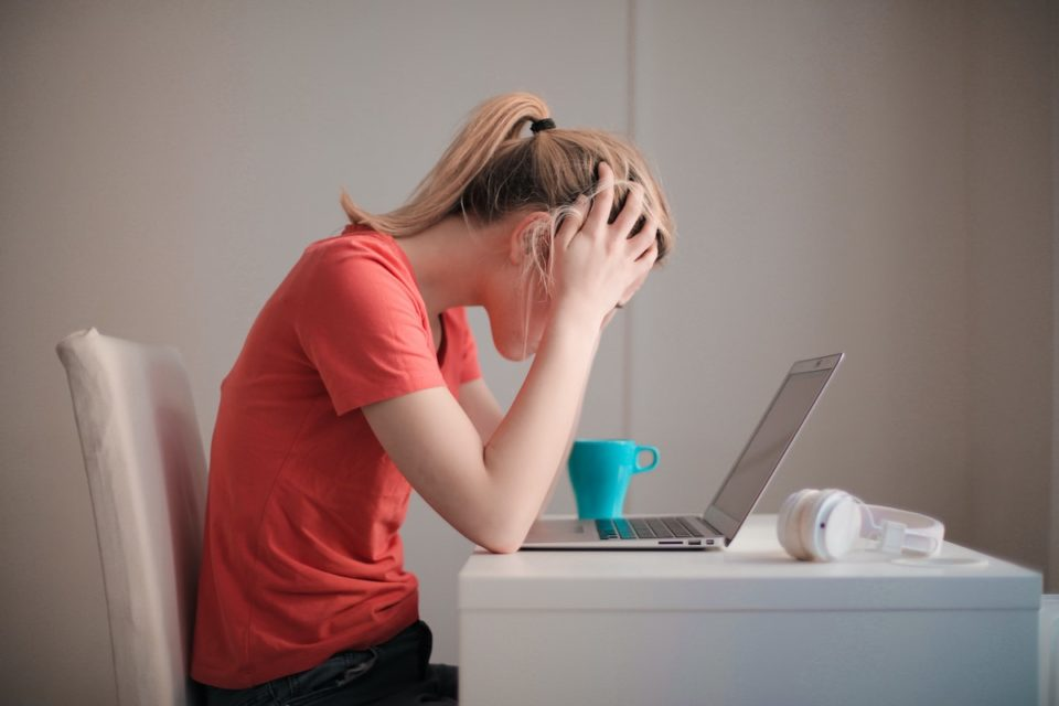 Frustrated young woman sitting in front of laptop with hands on head going over student loan debt.