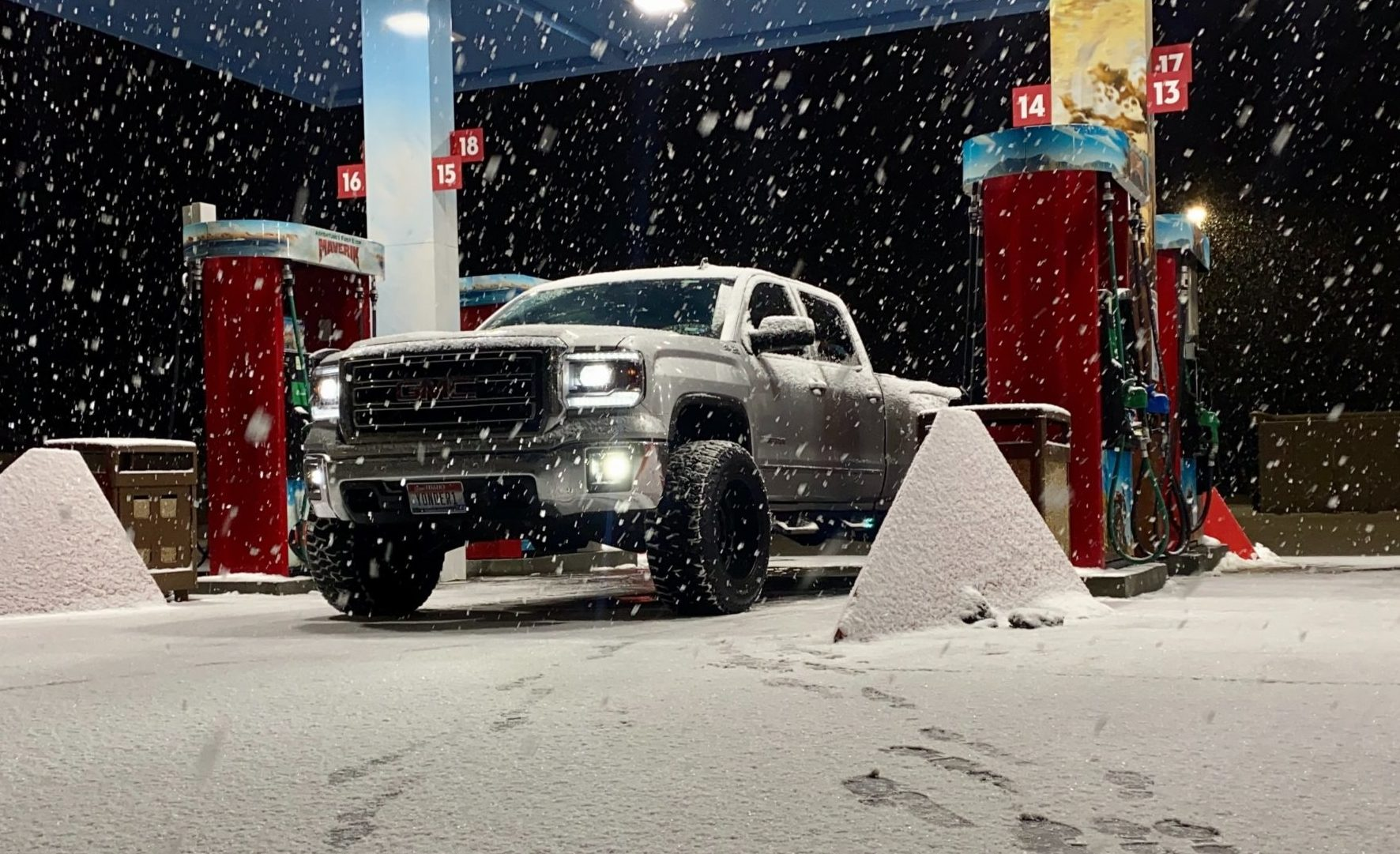 GMC truck in snow at the gas pump.