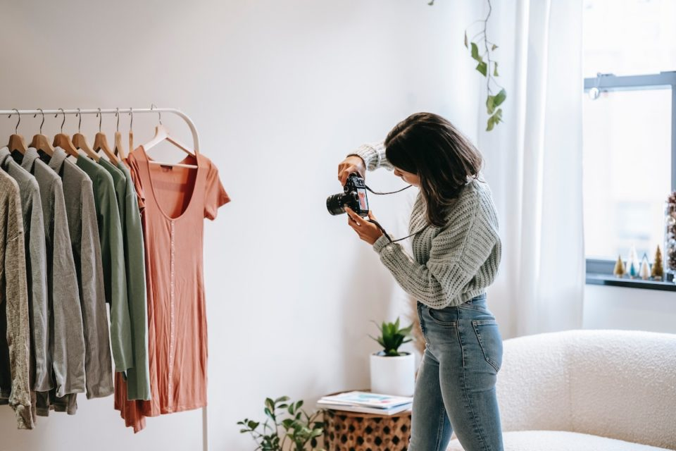 Woman taking photos of clothing for her side hustle..