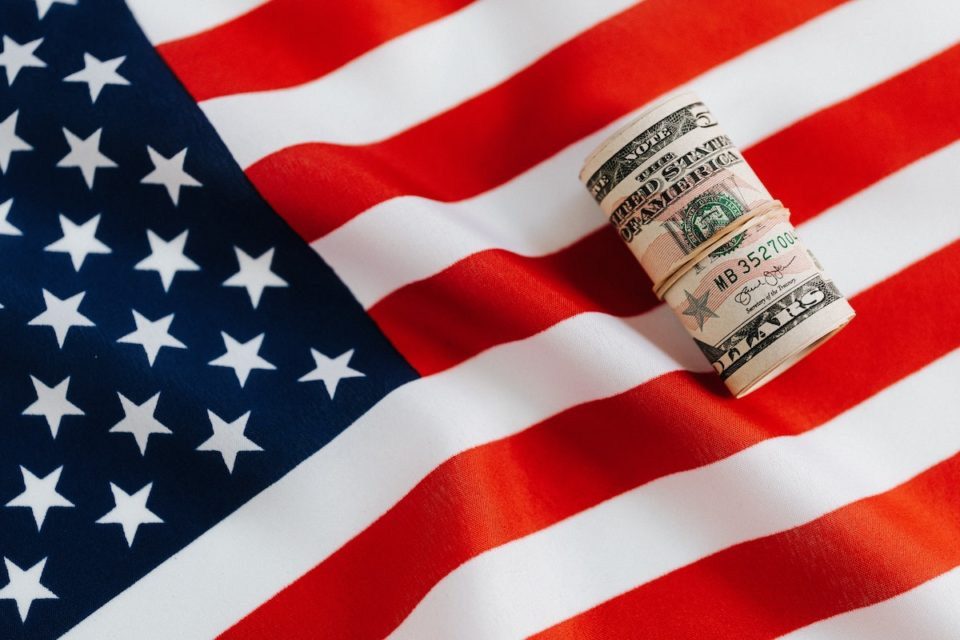 An American flag with a wad of rolled up cash for which stated pay the highest minimum wage.